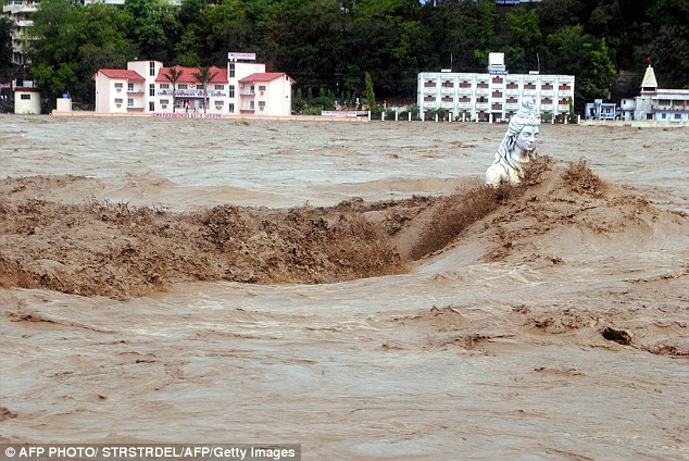 Fast moving water flows over a Hindu statue during a heavy monsoon rain in Rishikesh town in the Indian state of Uttrakhand