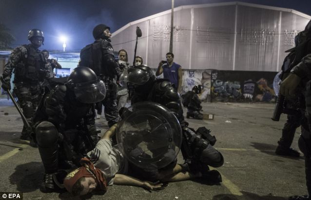 Caught: Police detain a protestor during clashes between both sides following trouble in Rio