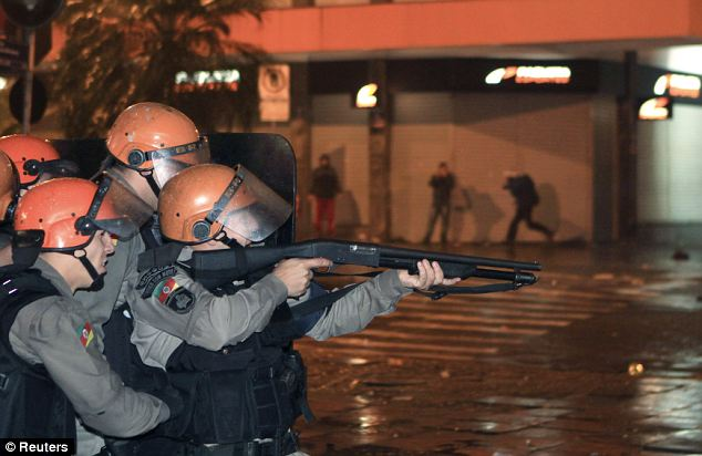 Countrywide civil unrest: Riot police aim their weapons at demonstrators during an anti-government protest in Porto Alegre, southern Brazil