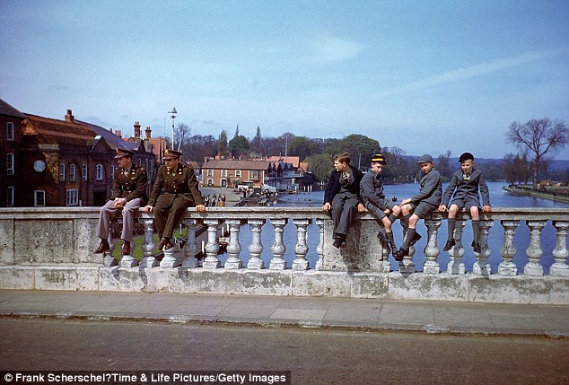 Troops and civilians pass the time on Henley Bridge, Henley-on-Thames, in 1944