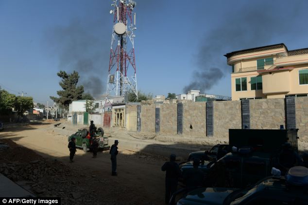 Battle: Afghan security forces stand guard as smoke rises from the entrance gate of the Presidential palace in Kabul