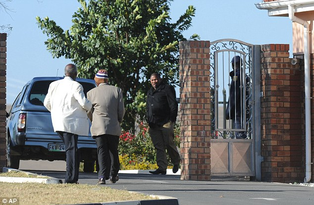 Meeting: Pedestrians and a vehicle are seen at the entrance to the homestead of former president Nelson Mandela in Qunu, South Africa, as close relatives were locked in a meeting at the property in Eastern Cape province