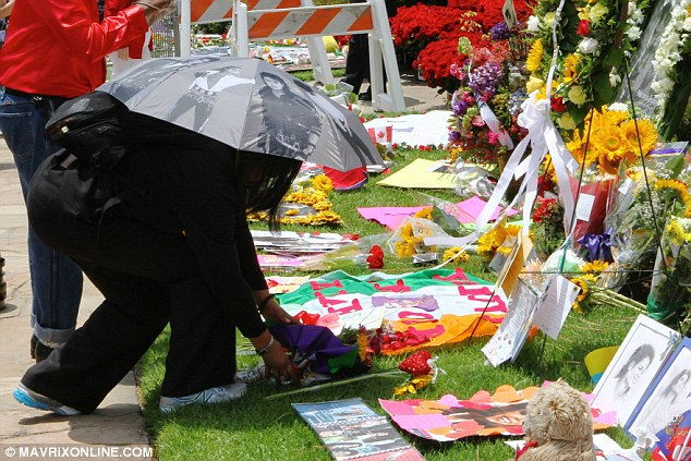 Never forget: A fan with a Jackson printed umbrella lays a tribute amongst the banners, photographs, soft toys and flowers