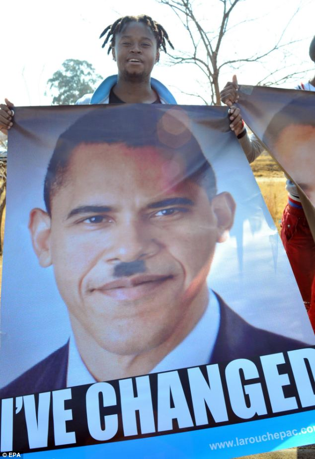 A protester holds a huge poster depicting US President Barack Obama wearing a toothbrush moustache and reading 'I've changed' during a demonstration against Obama's visit to the University of Johannesburg on Saturday