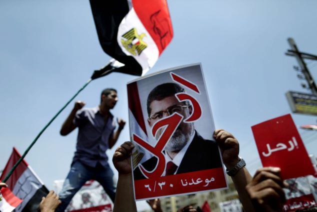 Opponents of Egypt's Islamist President Mohammed Morsi hold posters which read 'Leave' as they protest outside the presidential palace in Cairo