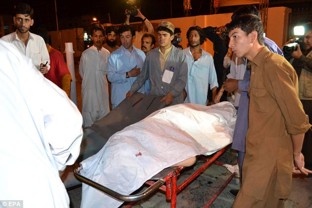 Murder: People shift bodies of the victims of a suicide attack targeting Shi'ite Muslims in Quetta, Pakistan