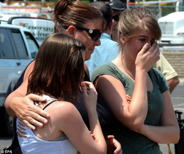 Tears: A group of girls cry after placing flowers at a make-shift memorial outside the Prescott fire station