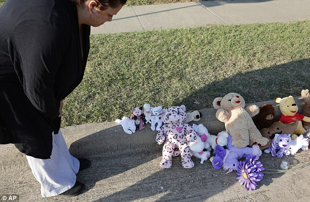 Coping: Neighbors quickly set up a makeshift memorial on the curb for the little girl, whose identity remains a mystery
