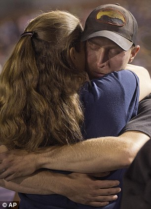 Vigil: Firefighter Brendan McDonough embraces a mourner near the end of a candlelight vigil in Prescott, Arizona on Tuesday, July 2, 2013