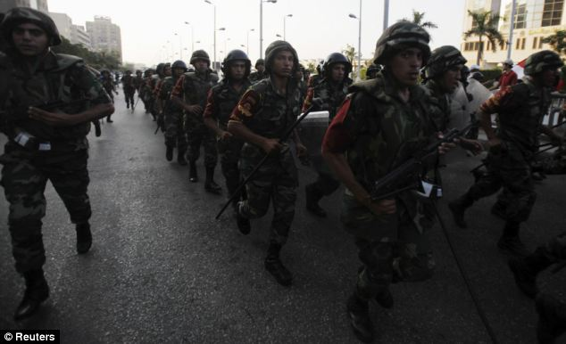 Army soldiers take their positions in front of anti-Morsi protestors near the Republican Guard headquarters in Cairo