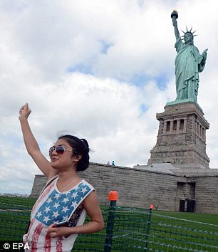 Grand re-opening: Hundreds of visitors poured into Liberty Island on Thursday to celebrate the re-opening of the Statue of Liberty to tours - eight months after Superstorm Sandy