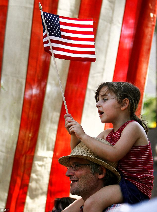 Embracing the flag: Ila Gocke sings while on her father's shoulders at a Durham, North Carolina parade