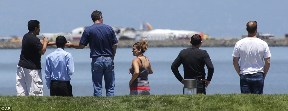 Shock: People look across the water at the wreckage of the plane, which crash landed on Saturday morning