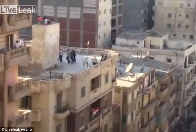 Terror: The video, apparently filmed with a mobile phone camera from a rooftop across the road, show the four teenage boys escaping onto a 20ft ledge atop a roof in Alexandria as the mob gathers around them