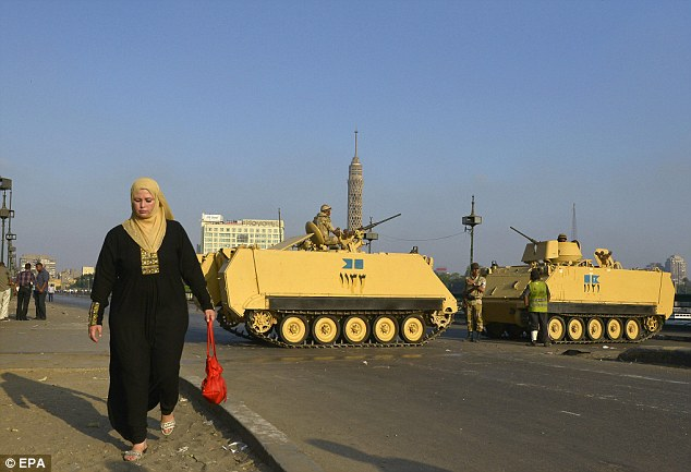 Unrest: An Egyptian woman walks past army forces on a bridge leading to Tahrir square in Cairo