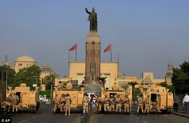 Brink of civil war: Egyptian army soldiers take their positions near armored vehicles at the entrance of Tahrir square in Cairo, where dozens of people were killed in clashes outside a military building in the capital