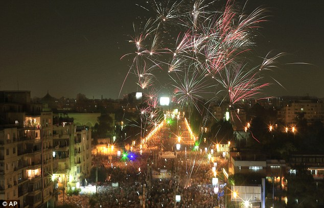 Explosive: Fireworks burst over opponents of Egypt's ousted Islamist President Mohammed Morsi during a rally outside the presidential palace in Cairo, where dozens of people have been killed in clashes