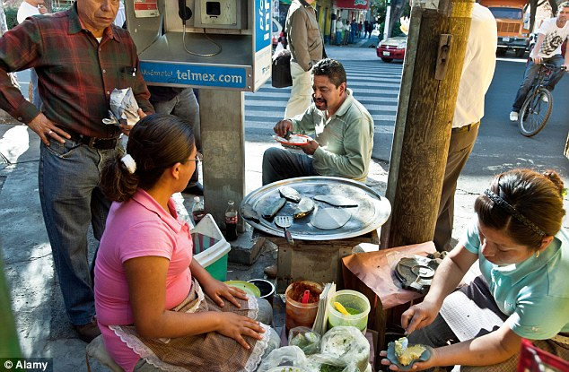 Street food: Cheap and tasty - two women preparing blue corn tacos surrounded by happy customers eating on busy street corner in the Roma district Mexico City