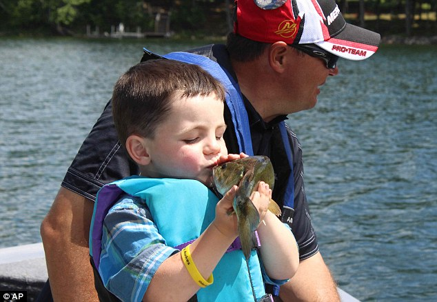 Angling for victory: America's youngest mayor, Bobby Tufts, kisses a fish on a trip on Lake Belle Taine in Minnesota as he takes time out from his campaign for a second term as head of the town of Dorset