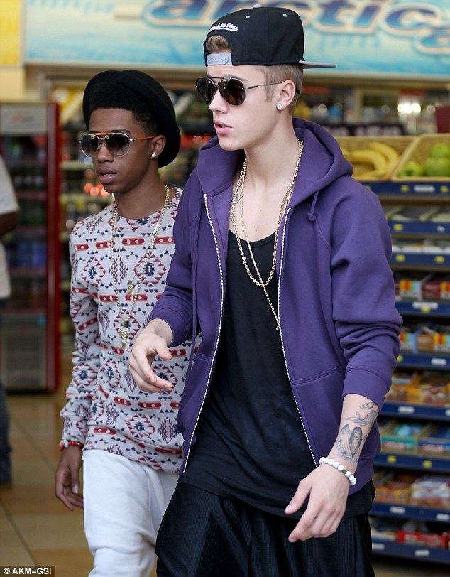 Stirring it up: Justin Bieber got a nightclub in trouble with Chicago police after they allowed him onto their age restricted premises, on Wednesday, pictured with Lil Twist in West Hollywood in May
