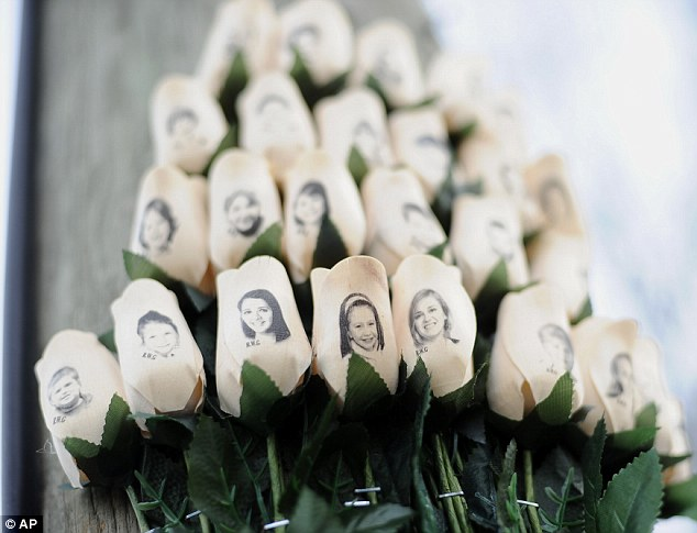 In this Jan. 14, 2013 file photo, white roses with the faces of victims of the Sandy Hook Elementary School shooting are attached to a telephone pole near the school on the one-month anniversary of the shooting