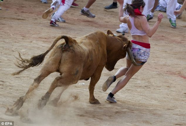 Sport: A young woman tries to outrun a the bull, but does not succeed, at the close of the running-with-the-bulls in the old city of Pamplona
