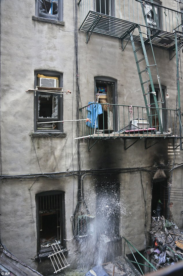 Disaster: Water sprays out through a window as firefighters throw out debris inside the Manhattan building