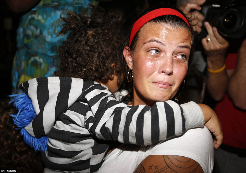A woman holding a child weeps outside of the courthouse after hearing the verdict announced