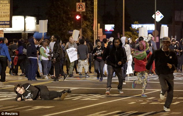 Trouble: A protester falls while others run as Los Angeles Police officers try to remove them from the intersection on Saturday