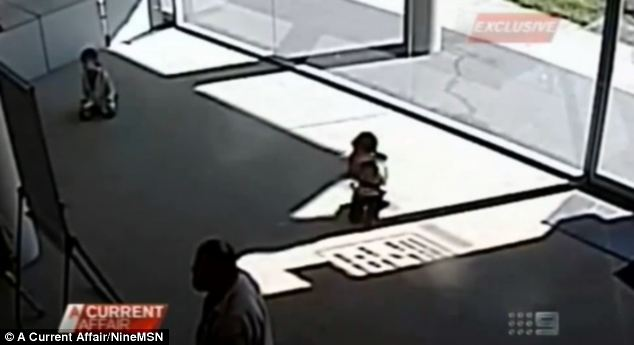 Terrifying: CCTV footage shows the boy and sister Zara (left) frozen in shock as robbers point guns at them