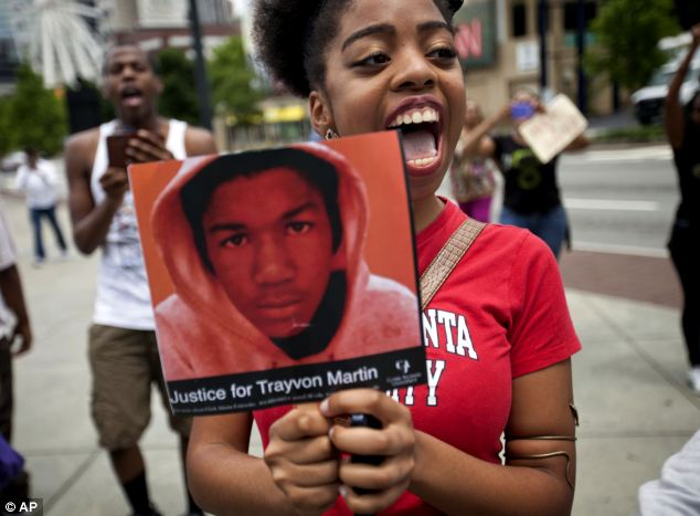 Outrage: Averri Liggins, 22, of Atlanta, holds a picture of Trayvon Martin during a protest over the verdict