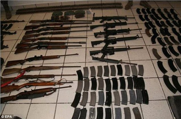 Cache: Weapons belonging to the Zetas cartel are displayed after they were found at the mass grave. The cartel has earned a brutal reputation in Mexico and across Central America and is controlled by former special forces soldiers
