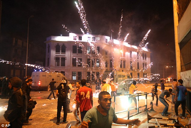 Chaos: Opponents of ousted President Mohammed Morsi flee from fireworks fired by pro-Morsi supporters during clashes on a bridge in downtown Cairo