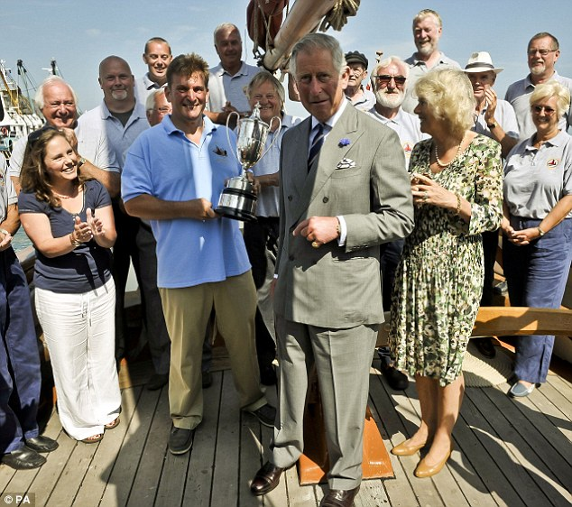 Annual visit: Charles and Camilla present the King George V Cup to the crew aboard restored fishing trawler The Pilgrim as the royal party is shown around heritage fishing vessels at Brixham Marina in the Devonshire fishing port of Brixham