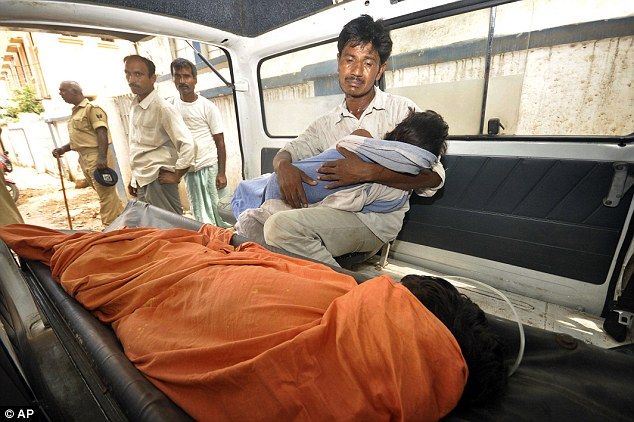 Horror: A father mourns as he holds his dead daughter today inside an ambulance, outside a hospital in Patna, in the eastern Indian state of Bihar