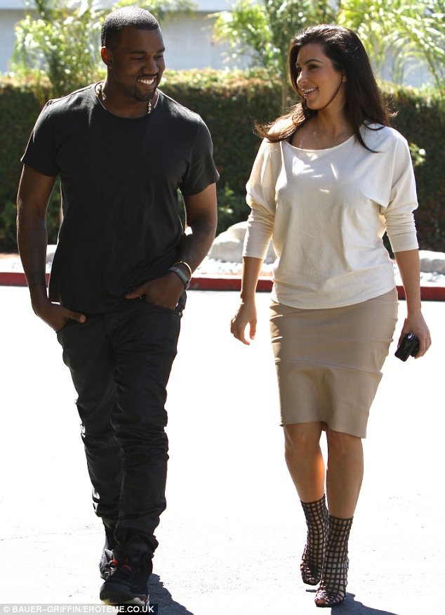 Bated breath: The world is awaiting a first glimpse of little North West. Her parents are seen here in July of last year