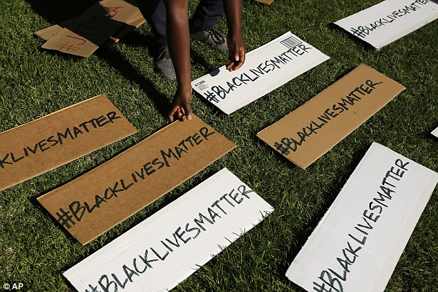 Poignant: A protester picks up signs that read '#BlackLivesMatter'