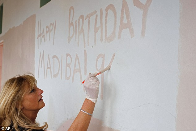 United: A woman paints a happy birthday message on a wall in Cape Town