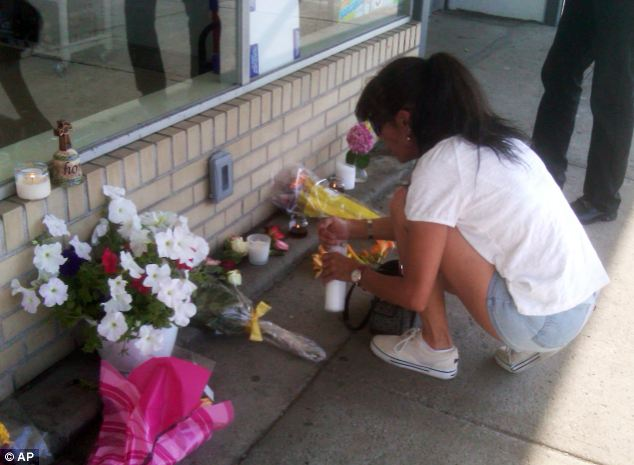 Sadness: Janet Post leaves flowers and lights a candle outside the Family Dollar store on Wednesday. She was in the store just a few hours before the fatal shooting and kidnapping