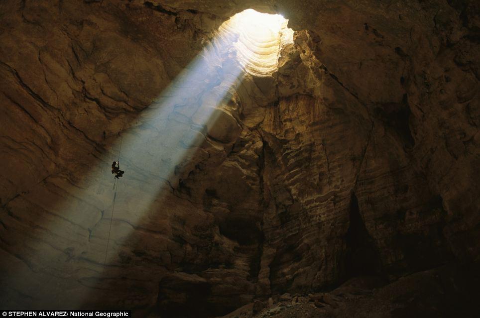 A man descends into Majlis al Jinn cave, Oman