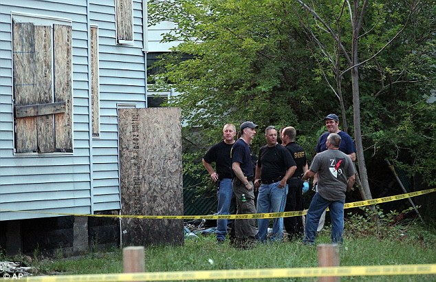 Grim discovery: Law enforcement and FBI stand at the back of a boarded-up home where bodies were found earlier in the day Saturday, July 20, 2013 in East Cleveland, Ohio