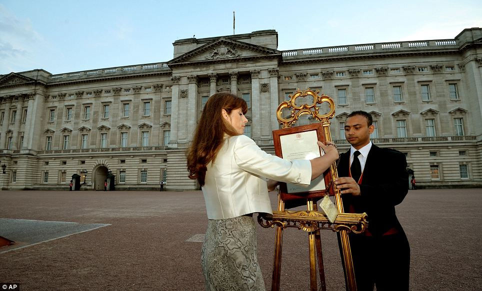 The Queen's Press Secretary Ailsa Anderson with Badar Azim, a footman, place the official document on the easel used in the same way when Prince William as born in 1982