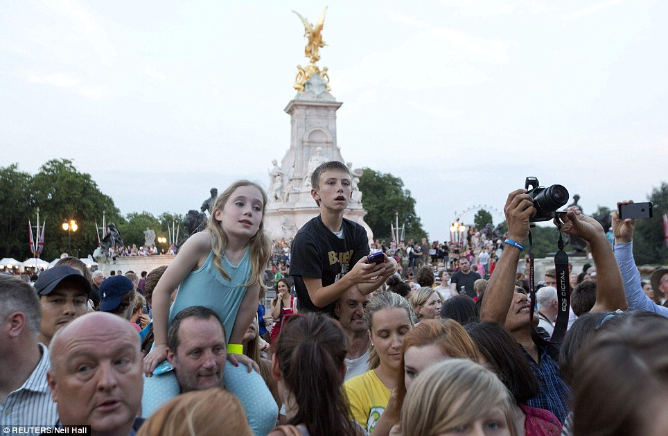 Fascinated: Two children in the crowd climb on adults' shoulders to grab a better view of the palace