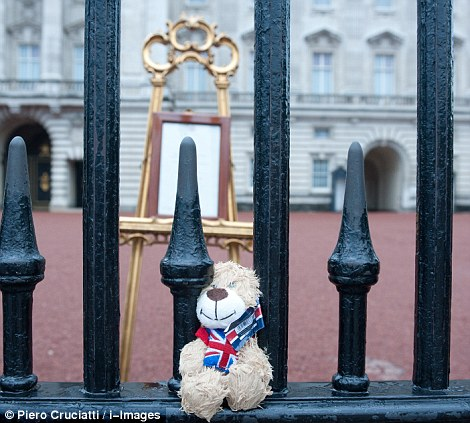 A teddy bear is left on the railings of Buckingham Palace where an easel has been placed