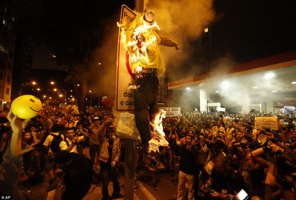 Contrast: Protests in Rio saw demonstrators burn a puppet that symbolises Rio de Janeiro state governor Sergio Cabral during a demonstration near Guanabara Palace