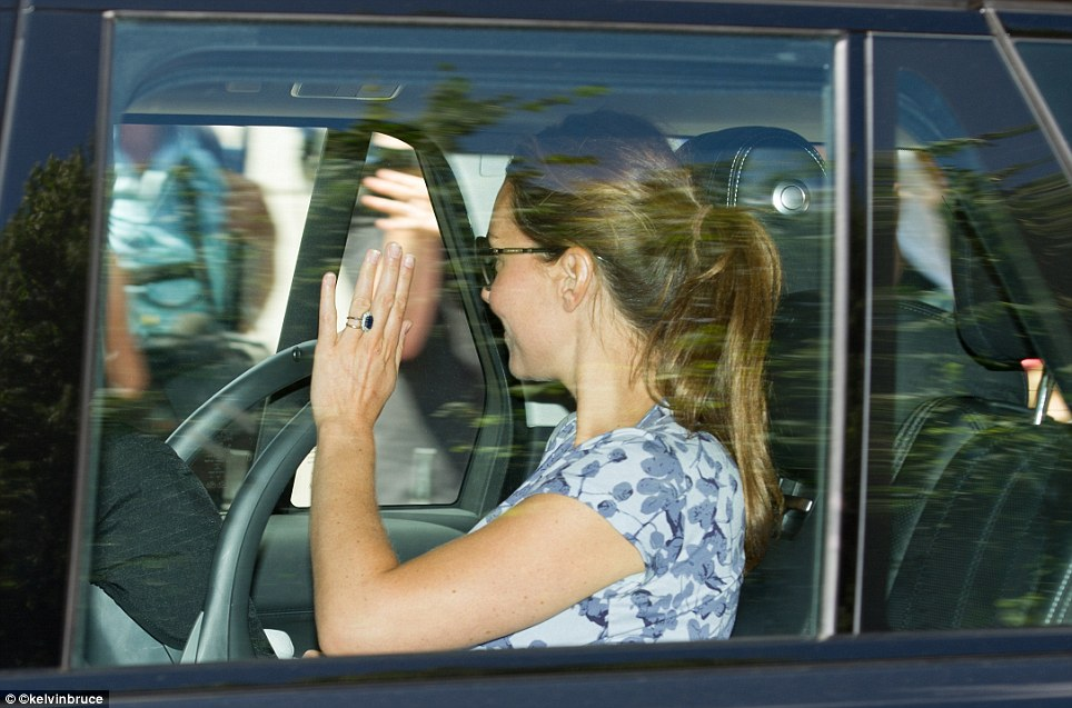 New mother: Kate waved with her left hand and appeared to have her right hand resting next to her baby