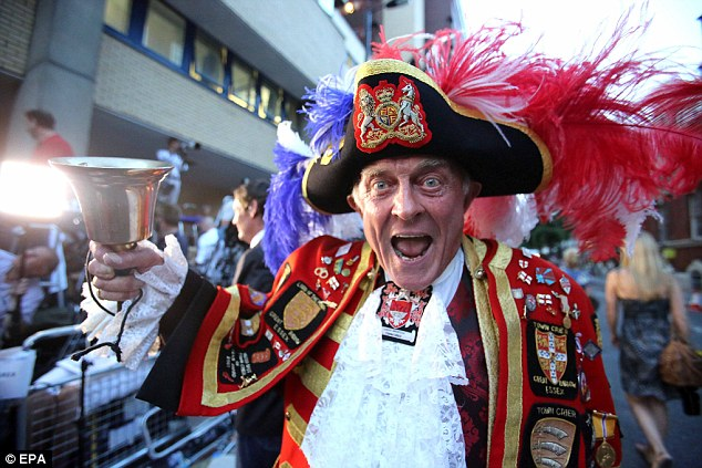 Self-proclaimed Town Crier Tony Appleton celebrates among the crowd outside St. Mary's hospital in London