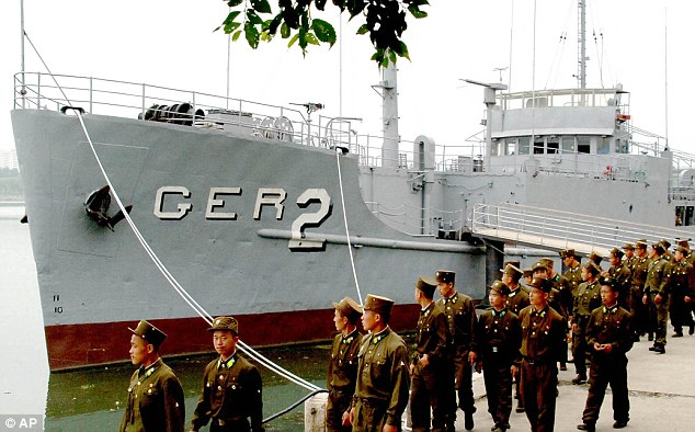Its a museum: The USS Pueblo sits on the banks of a Pyongyang, North Korea river as North korean soldiers walk past it