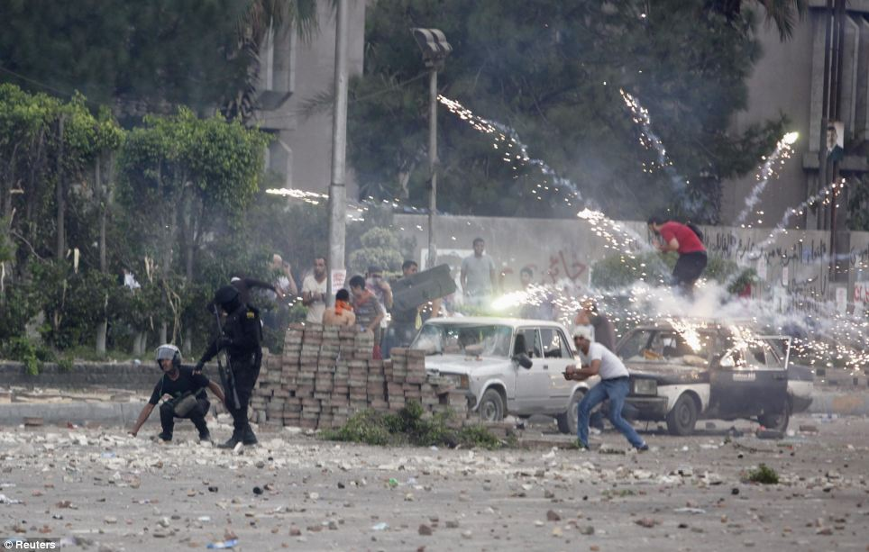 Explosion: Fireworks are set off near police and pro-army protesters by supporters of Morsi