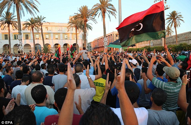 Anger: Libyans gather in a protest before attacking the National Forces Alliance office in Tripoli, Libya, today